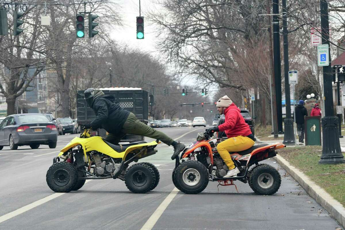A couple of men driving ATV's are seen crossing Madison Ave. from Washington Park on Friday, Jan. 22, 2021 in Albany, N.Y. (Lori Van Buren/Times Union)