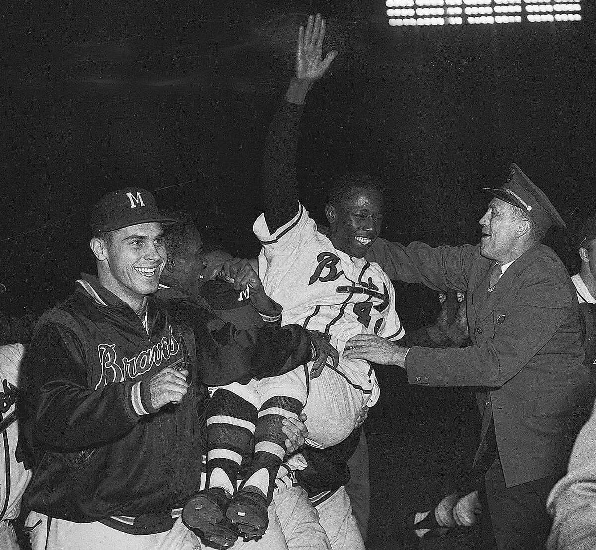 Hank Aaron is carried off the field by teammates after his home run against the Cardinals clinched the 1957 pennant for the Milwaukee Braves. Milwaukee went on to beat the Yankees in the World Series, with Aaron smashing three home runs there.