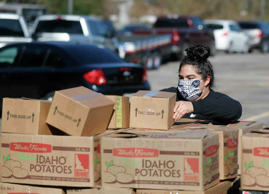 Sarah Bracamontes organizes boxes of pantry items while a line of vehicles snakes behind her as volunteers help distribute food for 200 families as part of YMCA's Mobile Market Food Drive in partnership with the Montgomery County Food Bank at Generations Church, Saturday, Jan. 9, 2021. Photo: Jason Fochtman, Houston Chronicle / Staff Photographer / 2021 © Houston Chronicle