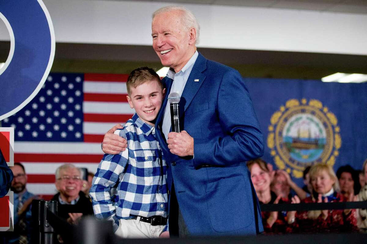 Then Democratic presidential candidate former Vice President Joe Biden hugs Brayden Harrington at a campaign stop in Gilford, N.H. on Feb. 10, 2020.
