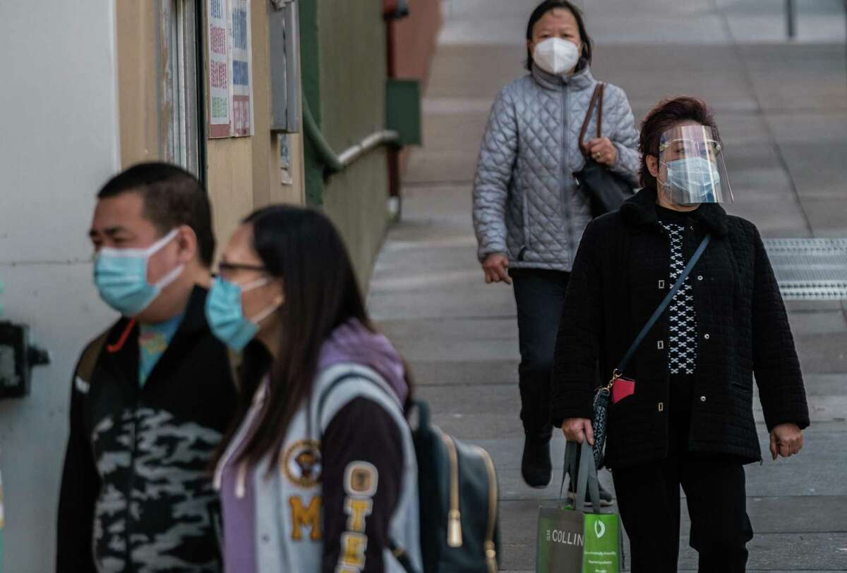 A woman wearing a face mask and a shield walks on a San Francisco sidewalk near other pedestrians wearing only face masks.