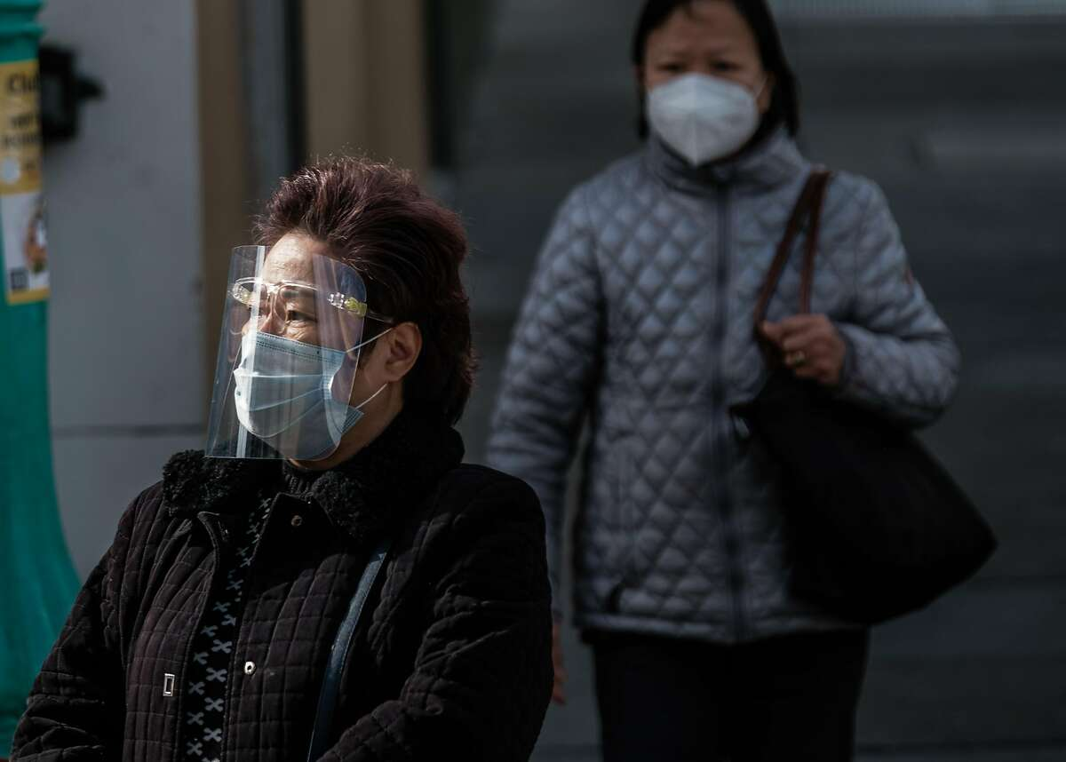 A woman wearing a face mask and shield crosses the street in San Francisco.