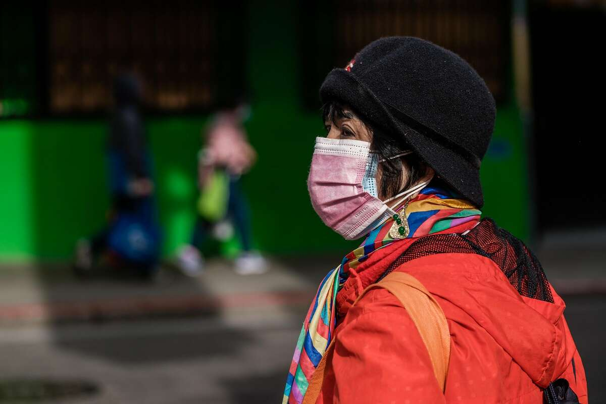 A woman wears two masks on a San Francisco street.