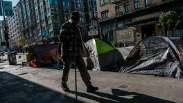 A pedestrian seen walking past a row of tents on the corner of Jones and Turk in San Francisco on Thursday, January 21, 2021. More tents have been popping up on sidewalks in the Tenderloin after a major push to get folks into temporary housing early on in the pandemic.