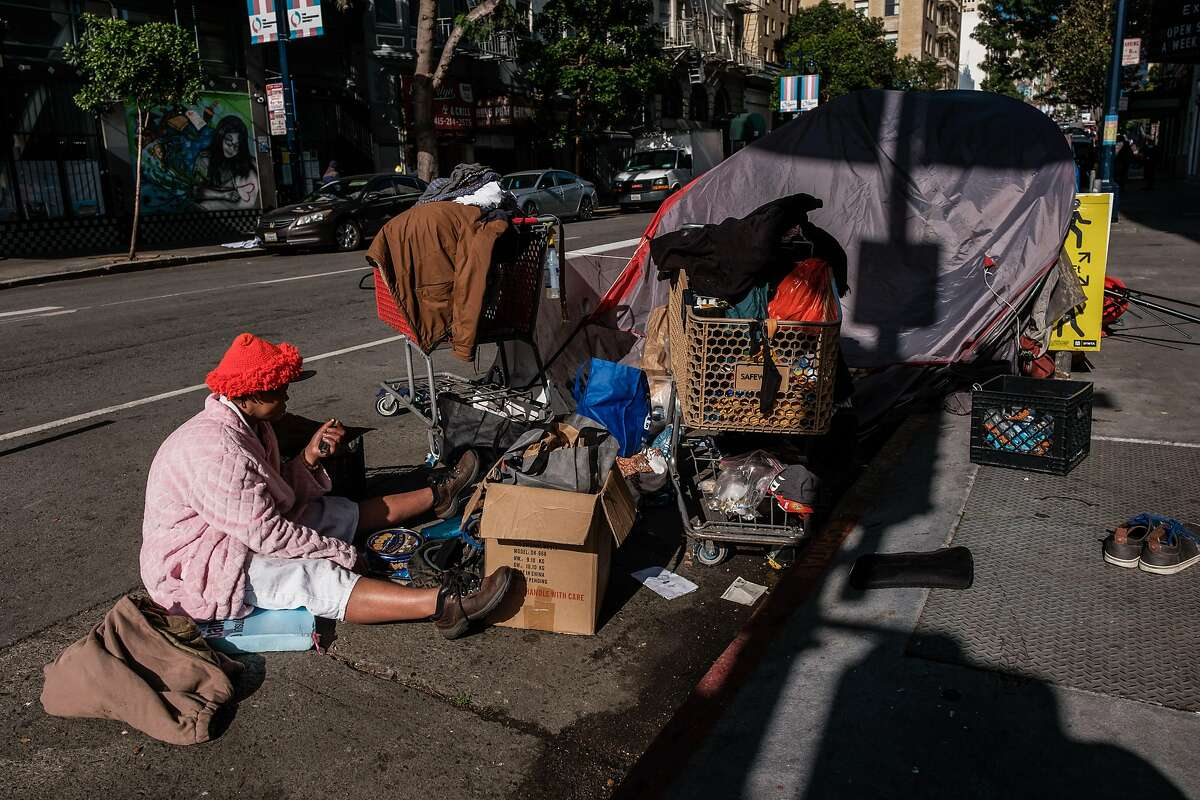 Ashley Zarinah Williams, 40, sits on the street next to her tent and belongings at Jones and Turk streets.