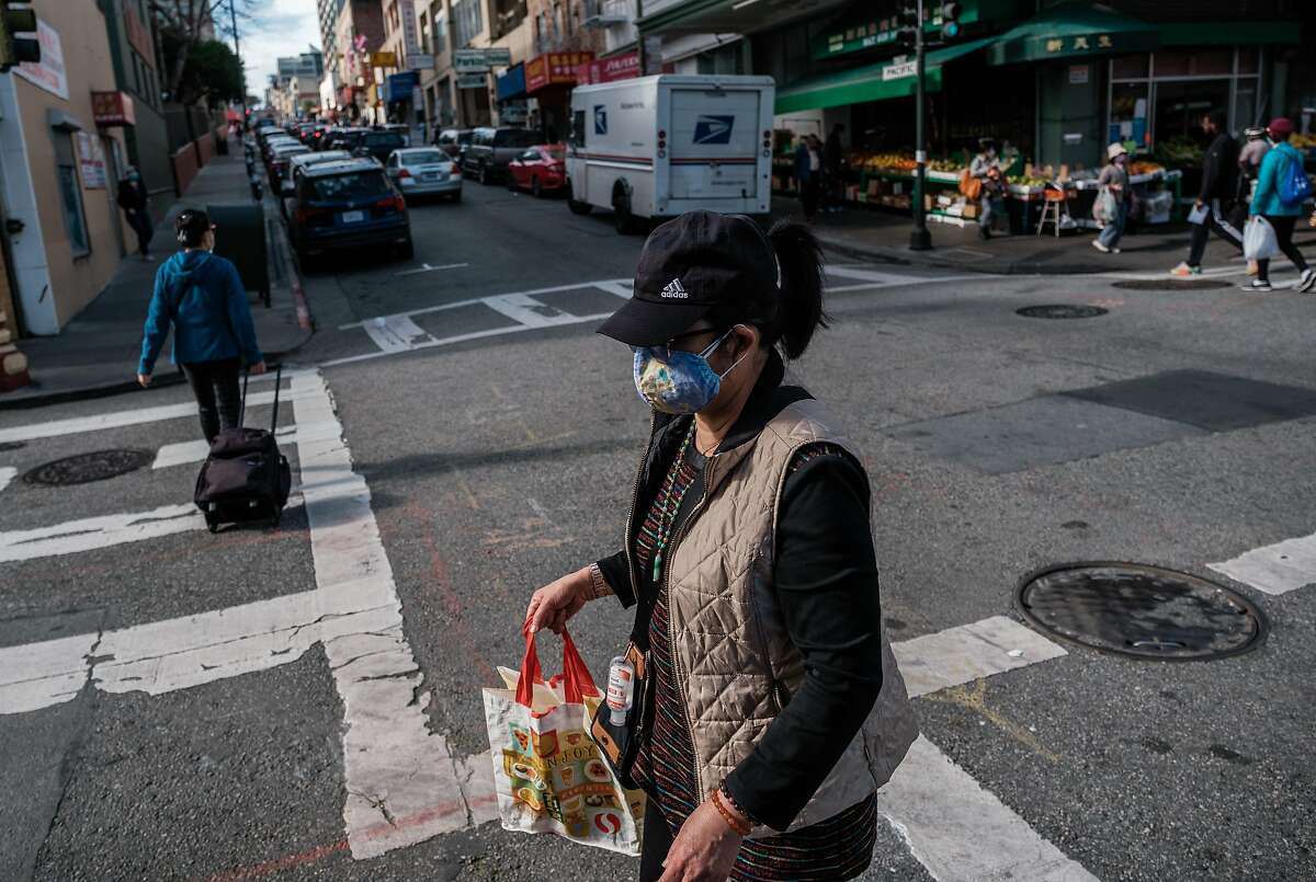 A woman wearing two masks, center, is seen crossing the street in San Francisco on Thursday, January 21, 2021.