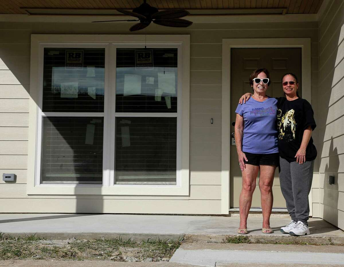 Barbara Rogers, center, and her daughter Christine Chuma stand in front of their rebuilt home in the Westbranch neighborhood.