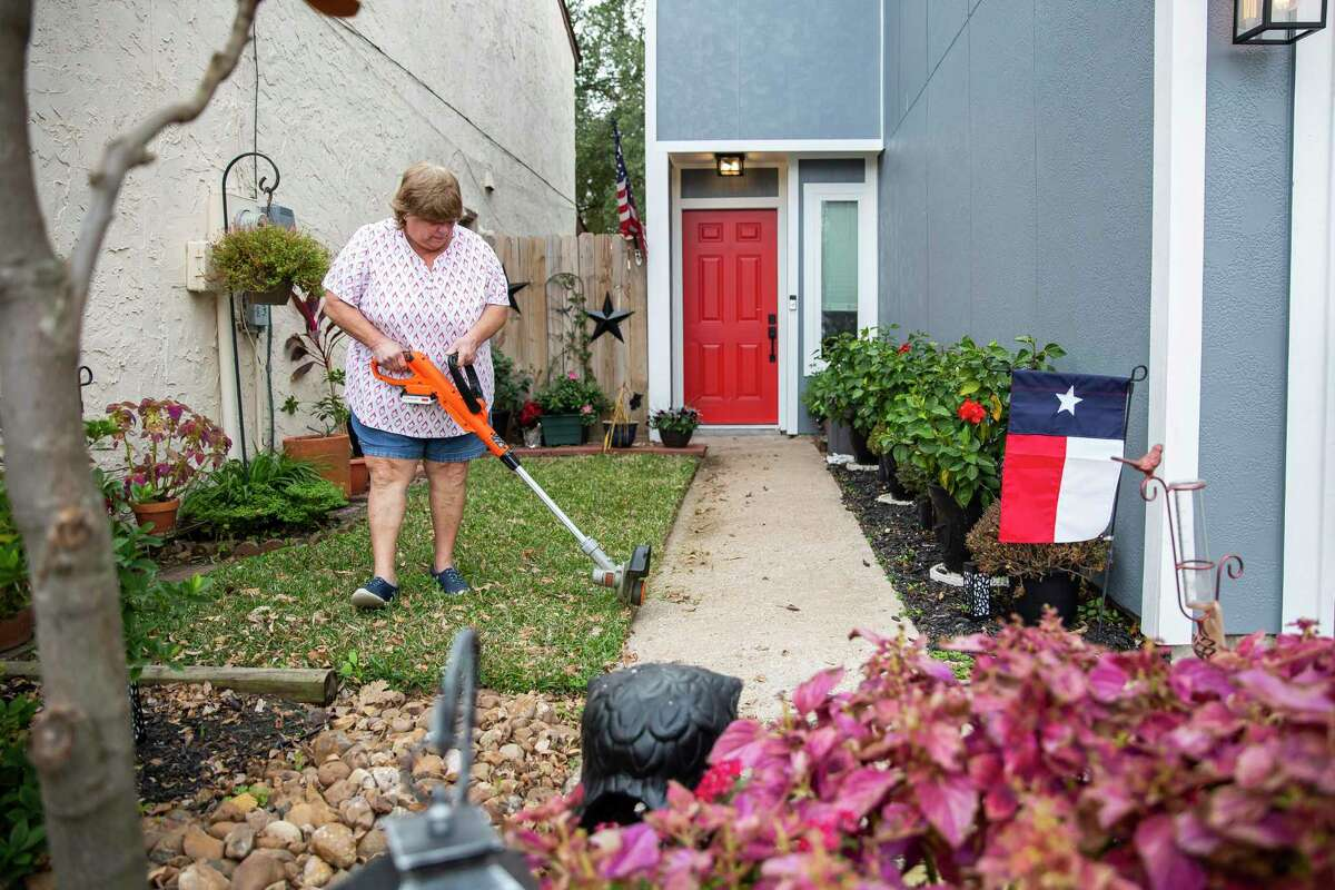 Suzanne Slavinsky works on her yard near the Watson Grinding & Manufacturing facility. Slavinsky and roommate Alicia Detamore were able to move back into their home in June, a few months after they watched their roof collapse as workers tried to repair it.