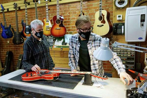 Marc Conley and Zach Potter of Quinn's Music put the final touches on a guitar repair on Tuesday afternoon. (Pioneer photo/Joe Judd)