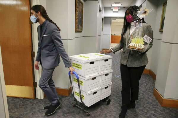 Co-founder Oji Martin (right) and Board member James Dykman of Fix SAPD bring boxes of 20,000 collected signatures for the city clerk to certify in hopes of putting the repeal of Chapter 174 on the May ballot on Friday, Jan. 8, 2021. The volunteer organization wants Chapters 174 and 143 which deal with collective bargaining and discipline procedures within the San Antonio Police Department - both of which FixSAPD want to repeal. Friday's presentation of 20,000 signatures was for the repeal of Chapter 174.