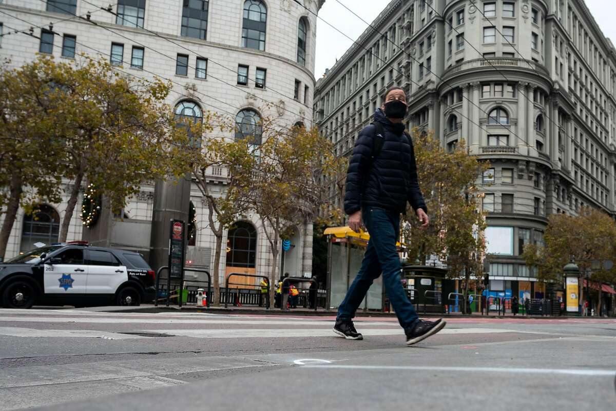 A pedestrian crosses Market Street at Fifth Street in San Francisco. San Francisco supervisors, the public health department and the city's transit agency are pushing street changes and using new funding to help prevent traffic deaths as they try to meet Vision Zero, the city's increasingly elusive goal of eliminating traffic fatalities by 2024.