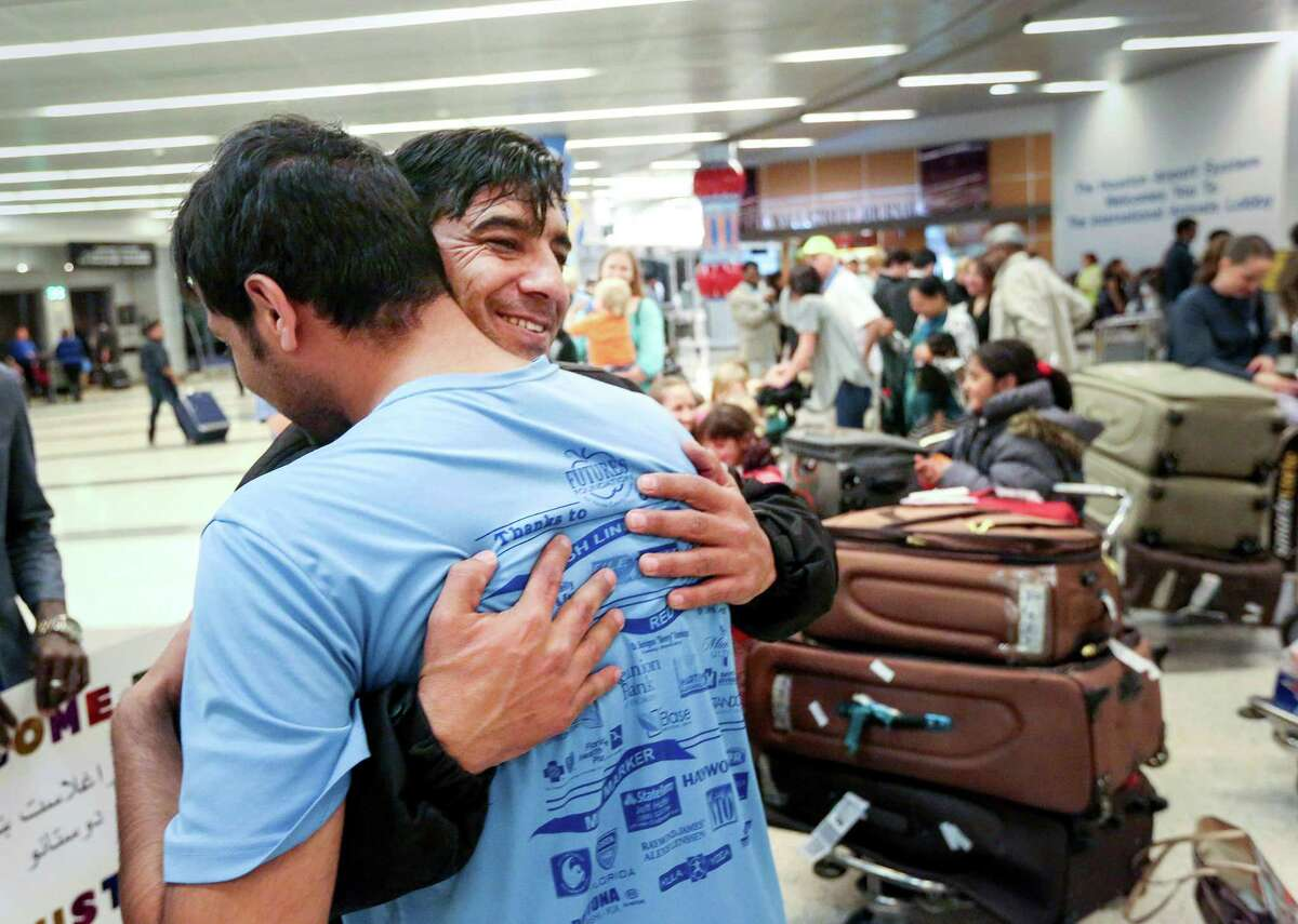 Noor, right, who came to the United States from Afghanistan under a Special Immigrant Visa with his wife and seven children, hugs his friend Mohammad Shakeb, as he arrives at BushIAH, Thursday, Feb. 9, 2017, in Houston. Noordid security work for American forces in Afghanistan. (JonShapley/ Houston Chronicle )