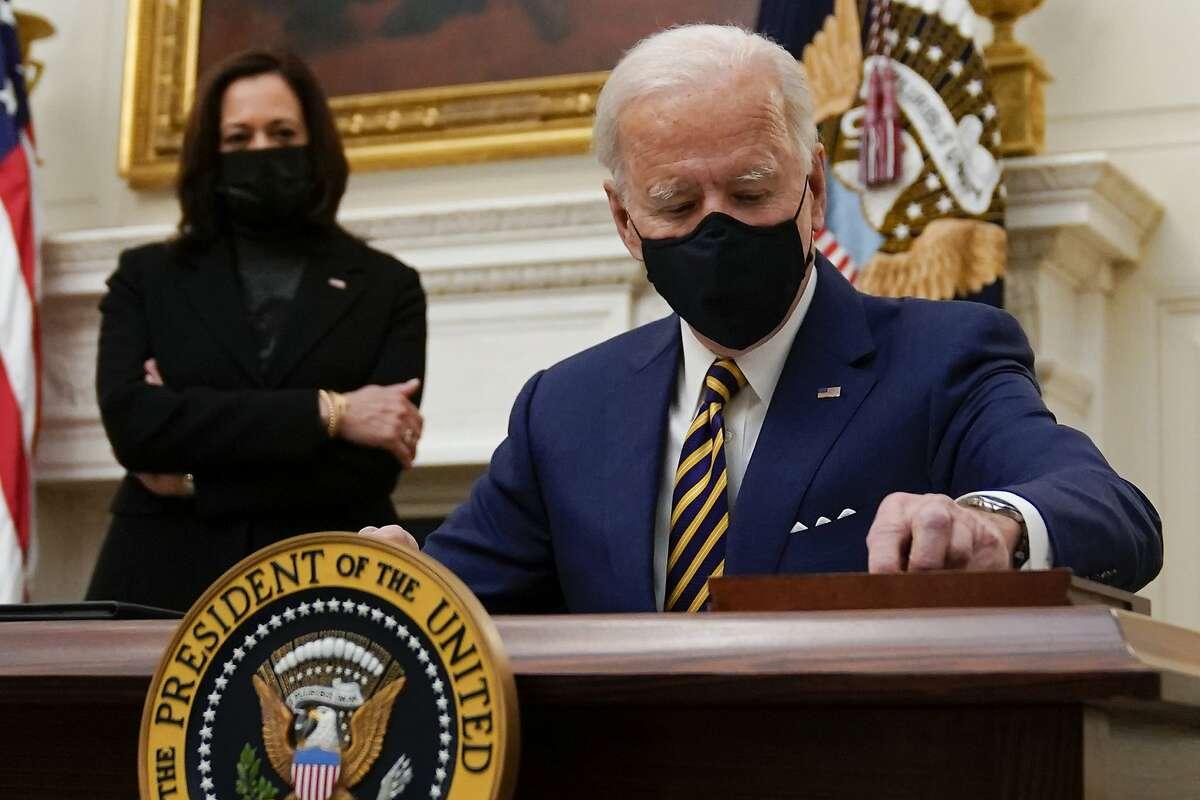 President Biden signs orders Friday as Vice President Kamala Harris looks on.