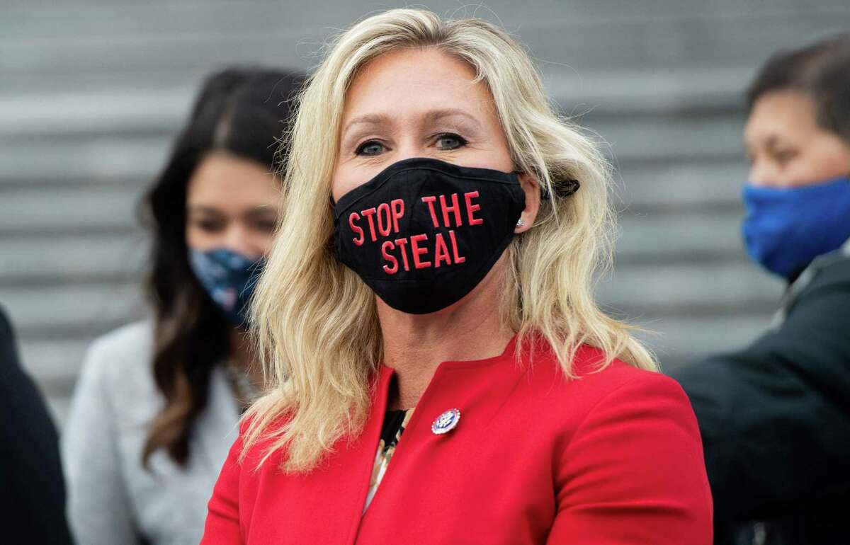 """US Representative Marjorie Taylor Greene, Republican of Georgia, holds up a """"Stop the Steal"""" mask while speaking with fellow first-term Republican members of Congress on the steps of the US Capitol in Washington, DC. - A newly elected Republican congresswoman known for promoting QAnon conspiracy theories accused Twitter of censorship on January 17, 2021 after her account was temporarily suspended for """"multiple violations"""". Marjorie Taylor Greene was hit with the 12-hour suspension after she tweeted claims of alleged election fraud in Georgia, her home state."""