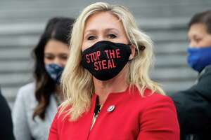 "US Representative Marjorie Taylor Greene, Republican of Georgia, holds up a ""Stop the Steal"" mask while speaking with fellow first-term Republican members of Congress on the steps of the US Capitol in Washington, DC. - A newly elected Republican congresswoman known for promoting QAnon conspiracy theories accused Twitter of censorship on January 17, 2021 after her account was temporarily suspended for ""multiple violations"". Marjorie Taylor Greene was hit with the 12-hour suspension after she tweeted claims of alleged election fraud in Georgia, her home state."