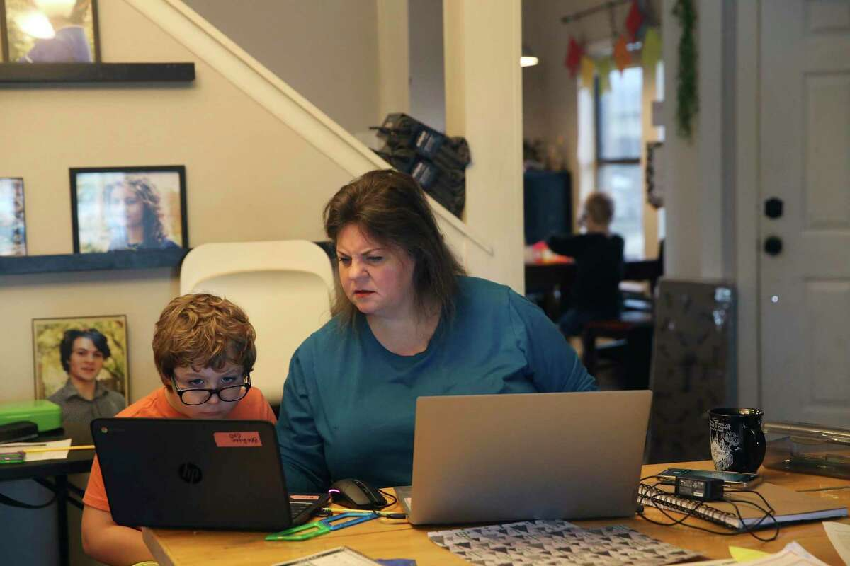 Sheila Ryan, 49, helps her son, Benjamin, 9, before the start of online class at their home, Friday, Jan. 22, 2021. Benjamin is fourth grader with Great Hearts Online, a charter school. She has six children in K-12 schools and three in college. Kids in remote learning are falling behind, especially in math. Some school districts have tested students to gauge the so-called COVID slide.