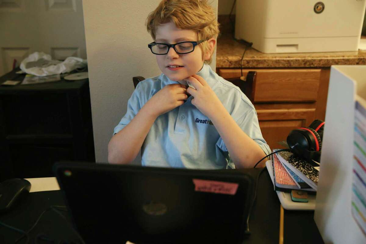 Judah Ryan, 11, buttons his polo before the start of online class at his family's home Friday. Ryan is a 5th grader at Great Hearts Online, a charter school. Kids in remote learning are falling behind, especially in math. Some school districts have tested students to gauge the so-called COVID slide. Judah presented a science project on the tundra biome.