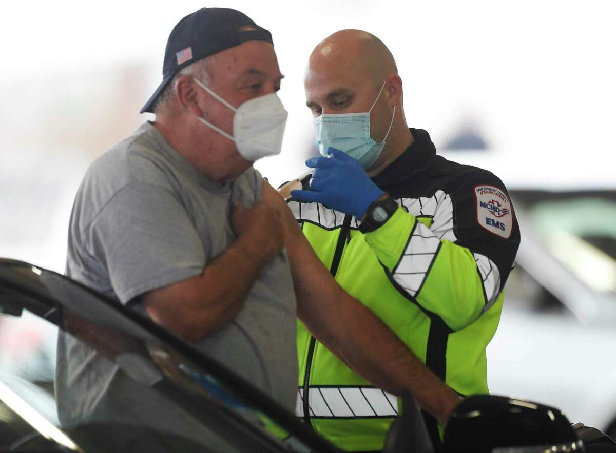 Montgomery County Hospital District paramedic Jade Campbell, right, administers the first dose of a COVID-19 vaccine to Joe Loucano at Montgomery County's first mass COVID-19 vaccination site at the Montgomery County Fairgrounds, Wednesday, Jan. 20, 2021, in Conroe.