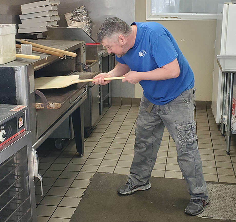Steve Walker cooks a pizza at The Pizza Crew. The restaurant offers carry-out for orders of pizza and wings. Photo: Photo Provided