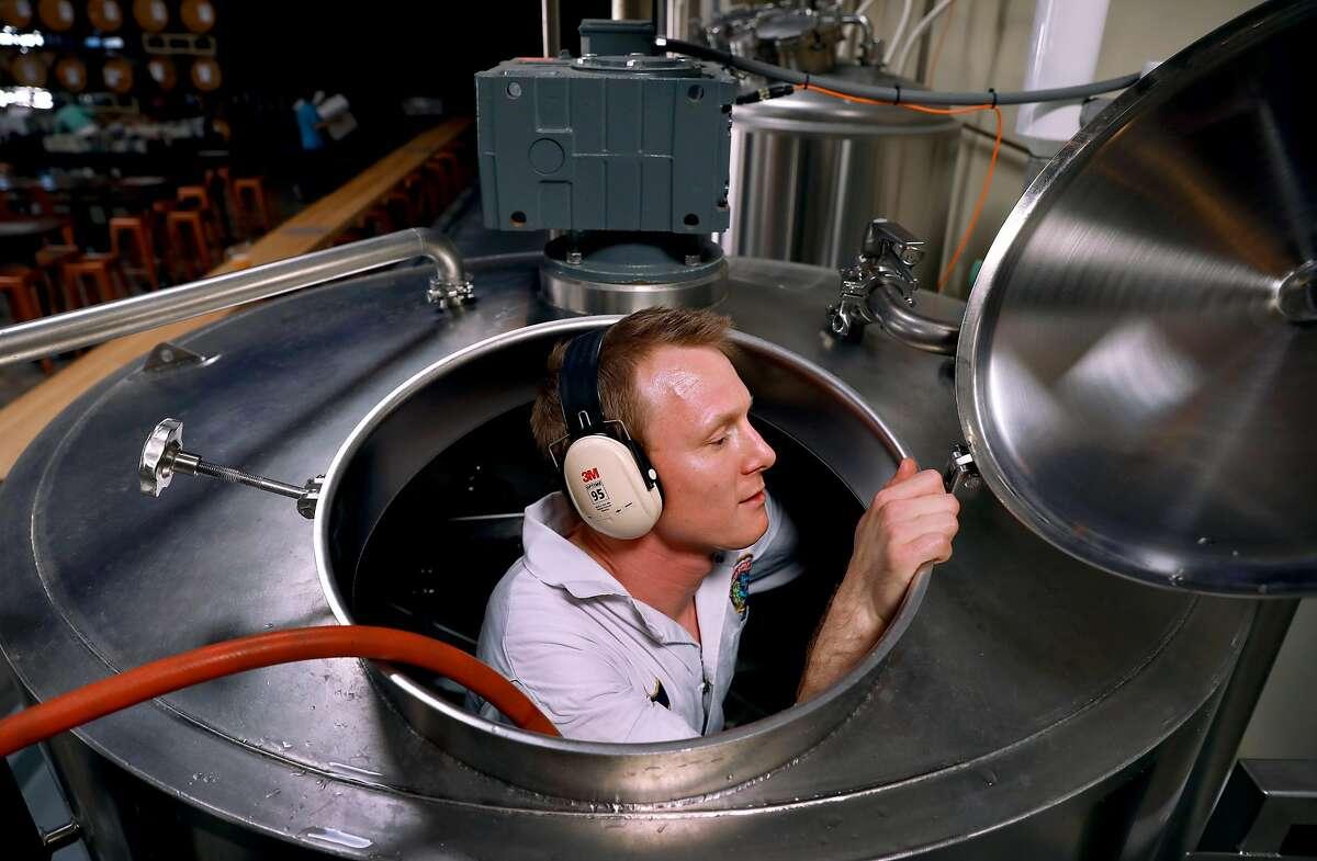 Pilot brewer Dane Volek cleans a brew kettle at Anchor Public Taps.