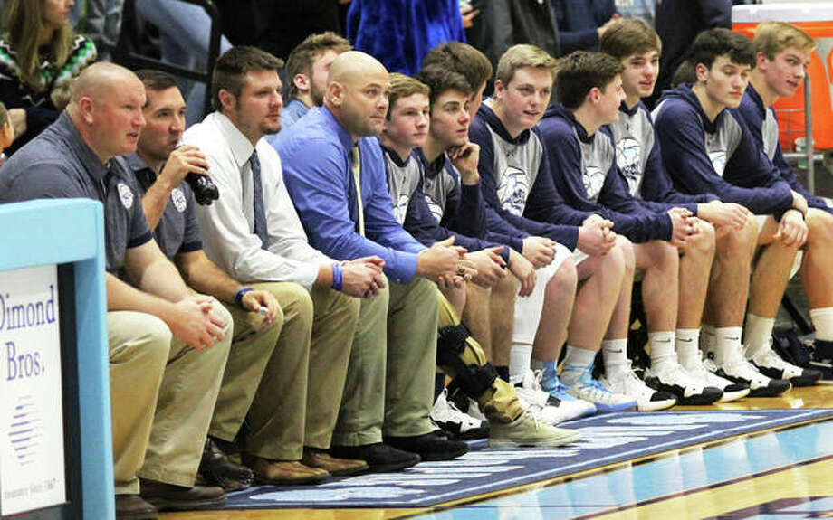 Jersey coach Stote Reeder (fourth from left), flanked by his assistants and team, watches a game from the bench two seasons ago at Havens Gym in Jerseyville. Friday's announcement from the Governor's office cleared a path for the Panthers and other basketball teams in Region 3 to begin their seasons. Photo: Greg Shashack | The Telegraph