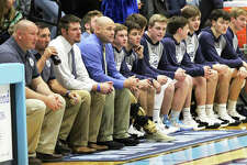 Jersey coach Stote Reeder (fourth from left), flanked by his assistants and team, watches a game from the bench two seasons ago at Havens Gym in Jerseyville. Friday's announcement from the Governor's office cleared a path for the Panthers and other basketball teams in Region 3 to begin their seasons.
