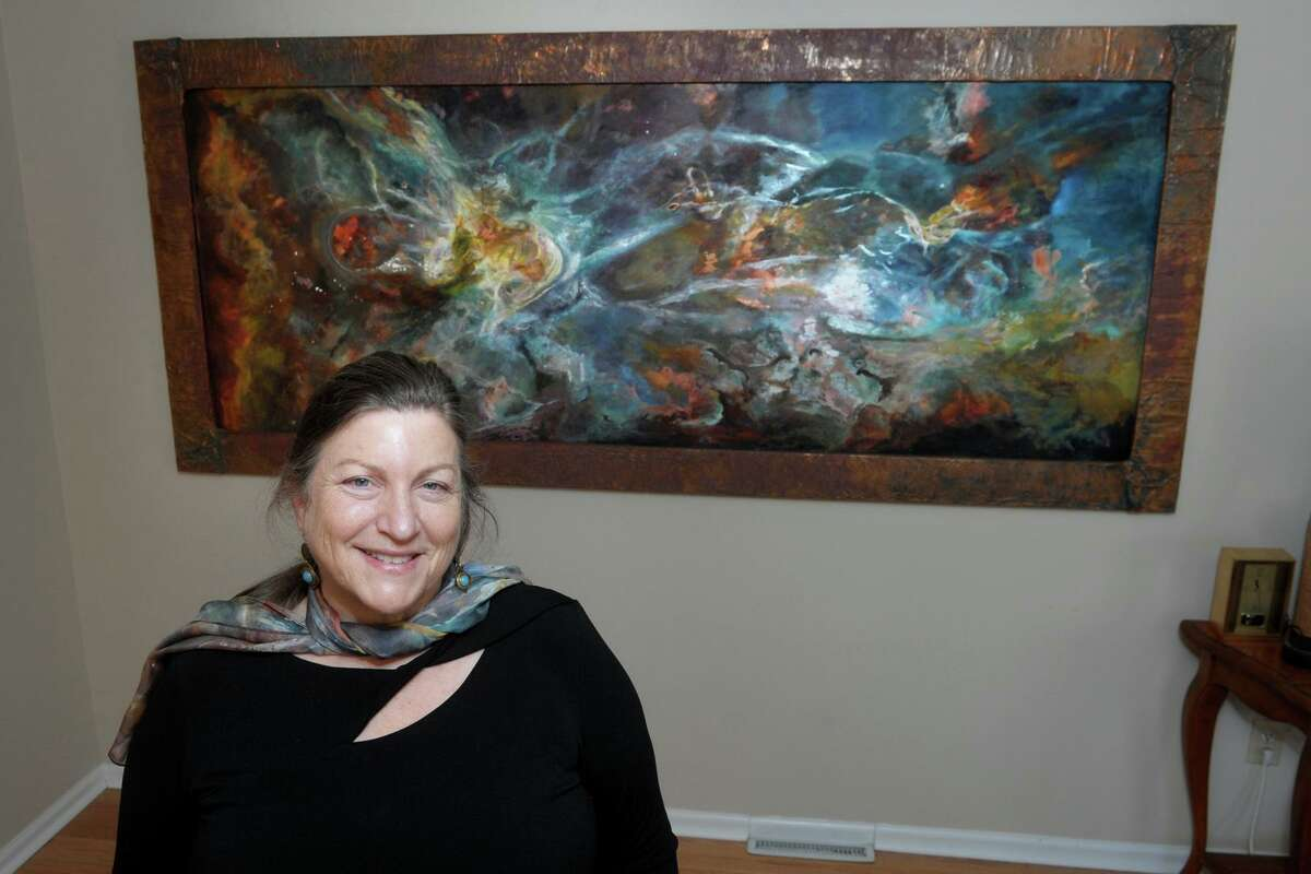 Jill Nichols poses in front of her painting 'Phi' in her home and studio in Shelton, Conn. Jan. 22, 2021. A copy of the painting currently hangs in the Vatican Observatory Museum.