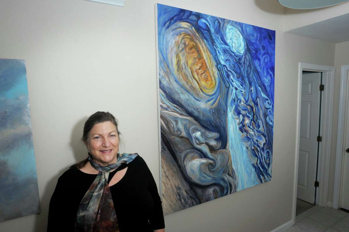 Jill Nichols poses in front of her painting 'Juno' in her home and studio in Shelton, Conn. Jan. 22, 2021. A copy of the painting currently hangs in the Vatican Observatory Museum.