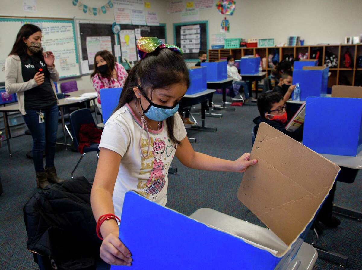 Third grader America Castillo, center, closes her privacy station as the class finished a test at Calder Road Elementary on Friday, Jan. 15, 2021, in Dickinson, Texas. Tens of thousands of students have opted to return to campuses for instruction despite a surge in COVID-19 infections. In Dickinson ISD, 93 percent of students are back in their classrooms.
