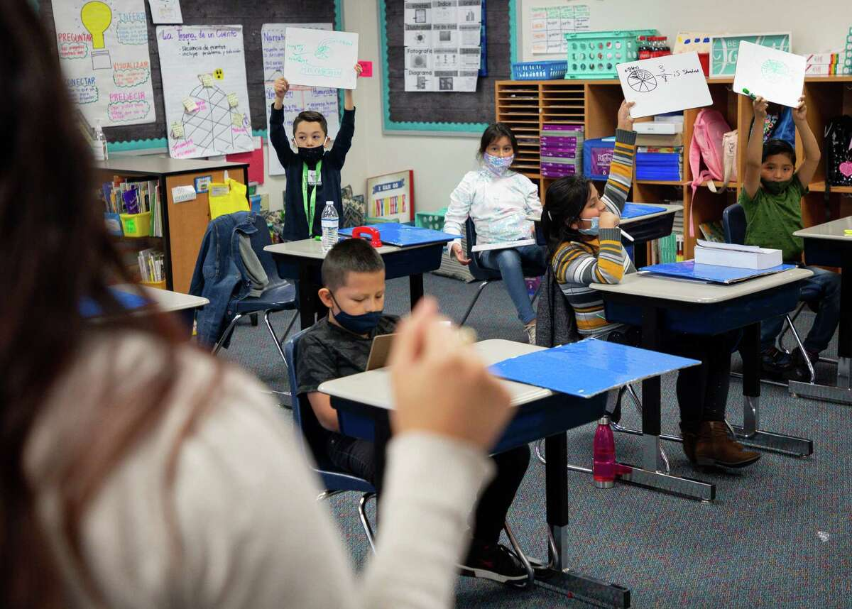 Third graders raise their answers at the request of their teacher Yadira Sesher, foreground, at Calder Road Elementary on Friday, Jan. 15, 2021, in Dickinson, Texas. More than 40,000 students have opted to return to campuses for instruction despite a surge in COVID-19 infections. In Dickinson ISD, 93 percent of students are back in their classrooms.