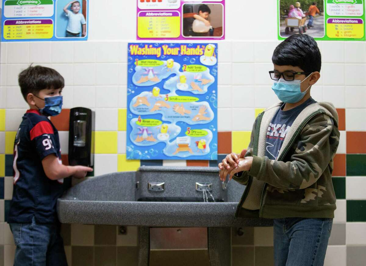 Third graders Aza Noriega, left, and Aadan Lopez, right, wash their hands after making a volcano model erupt at Calder Road Elementary on Friday, Jan. 15, 2021, in Dickinson, Texas. More than 40,000 students have opted to return to campuses for instruction despite a surge in COVID-19 infections. In Dickinson ISD, 93 percent of students are back in their classrooms.