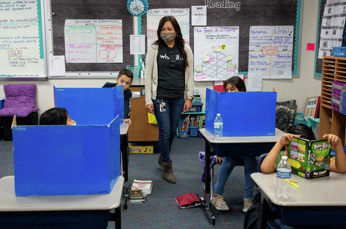 Third grade teacher Yadira Sesher, center, checks in on her students at Calder Road Elementary on Friday, Jan. 15, 2021, in Dickinson, Texas. More than 40,000 students have opted to return to campuses for instruction despite a surge in COVID-19 infections. In Dickinson ISD, 93 percent of students are back in their classrooms.