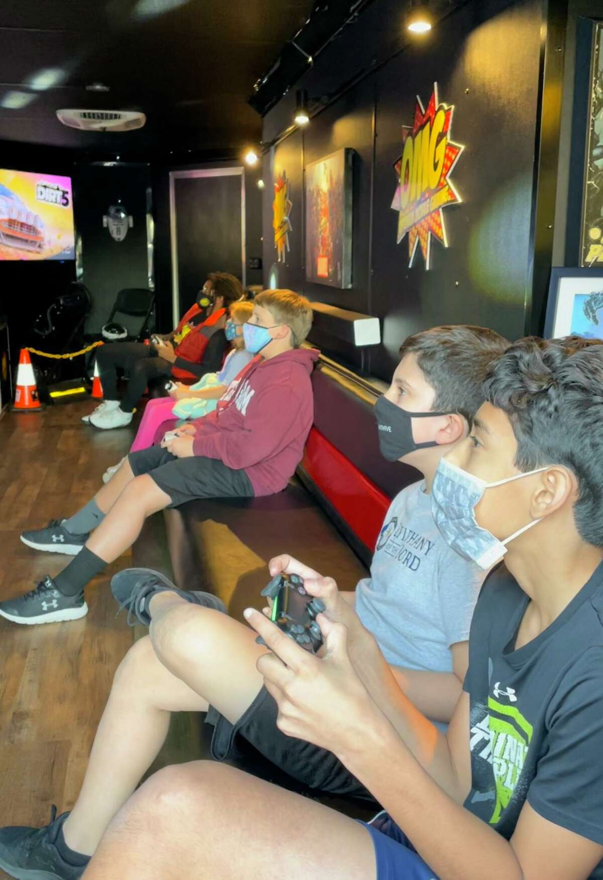 Children attending a birthday party play video games in Optimum Mobile Gaming's video game truck on Jan. 22, 2021.