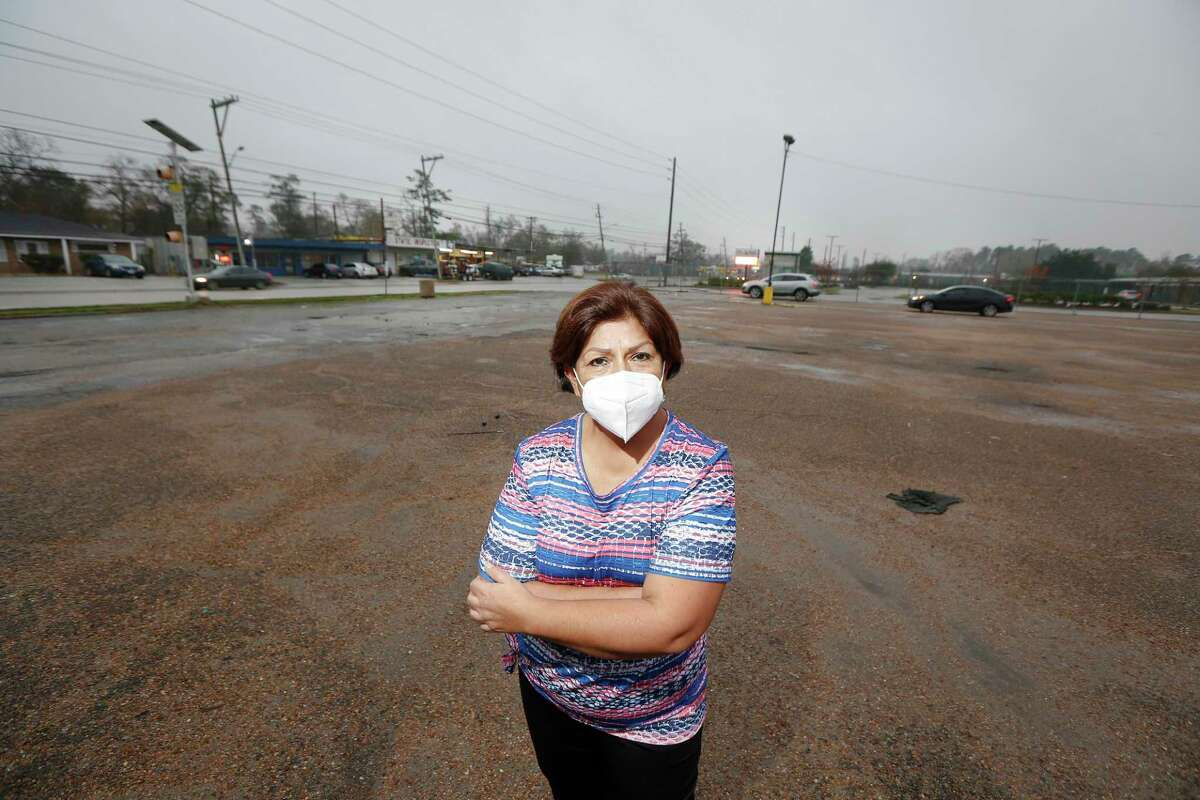 Myrtala Tristan stands in a parking lot across from her neighborhood that she said she had to wade or boat out during heavy rains Thursday, Jan. 21, 2021, in Houston.