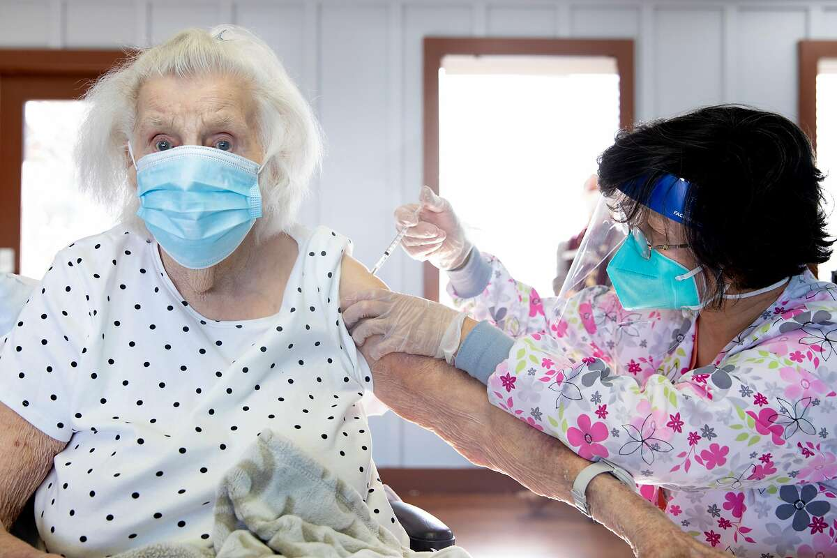 Edna Buel, 103, gets her first dose of the coronavirus vaccine from Rose Cheng while at her assisted living facility in Alameda.
