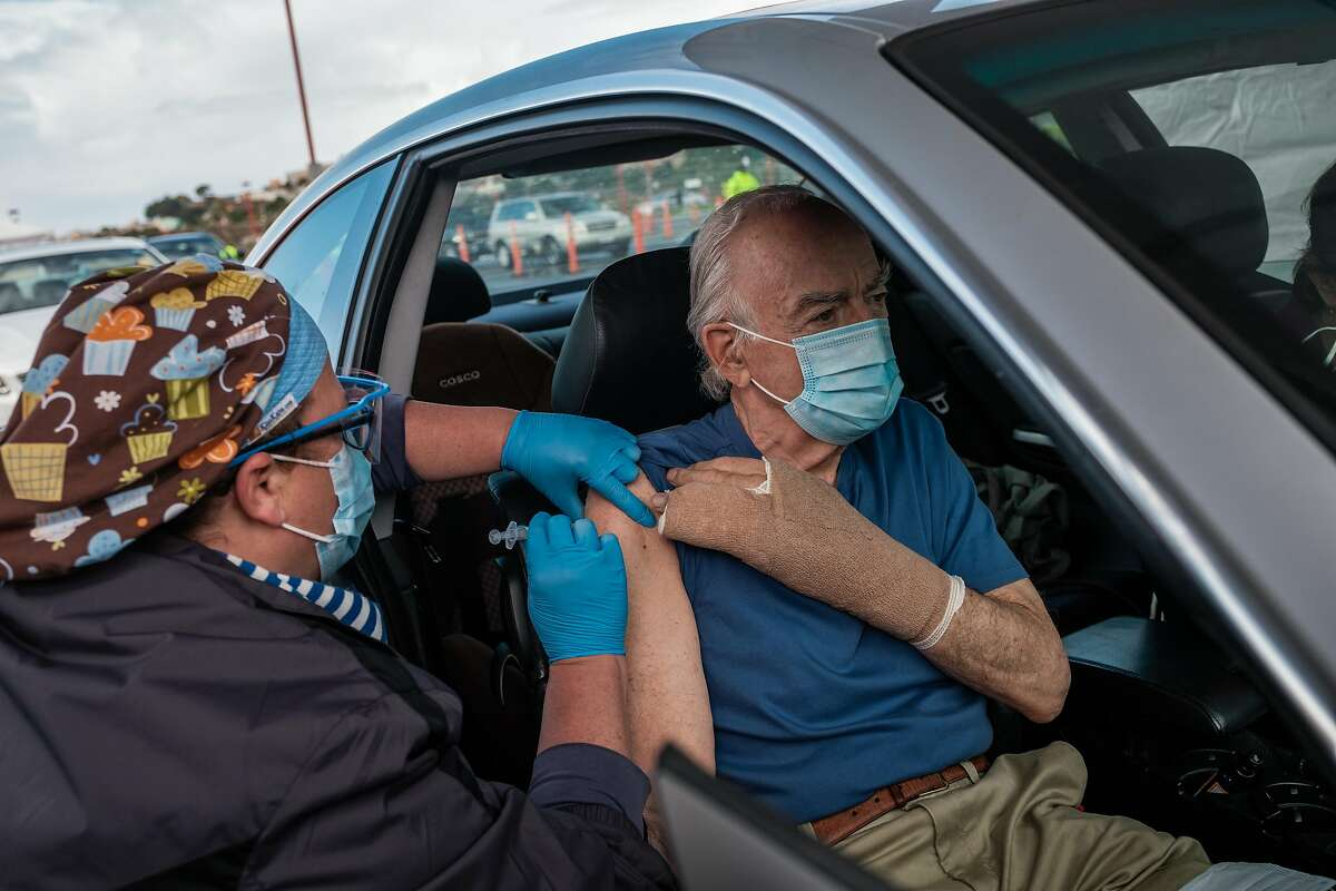 Above: Thomas Ballard receives a shot at a newly opened mass vaccination center at City College in San Francisco.