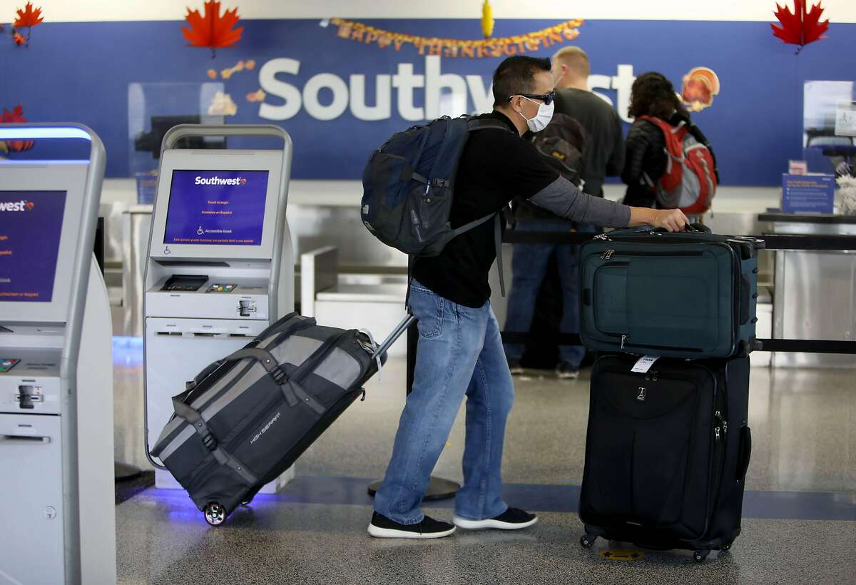 Travelers stand in line near the Southwest counter at the Oakland International Airport on Friday, November 13, 2020, in Oakland, Calif.