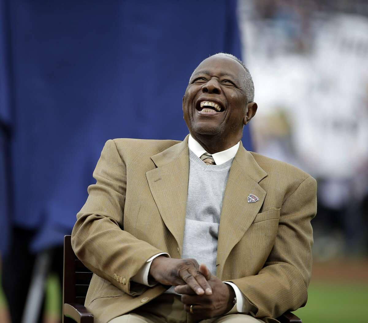 FILE- In this April 8, 2014, file photo, Hank Aaron laughs during a ceremony celebrating the 40th anniversary of his 715th home run before the start of a baseball game between the Atlanta Braves and the New York Mets in Atlanta. Hank Aaron, who endured racist threats with stoic dignity during his pursuit of Babe Ruth but went on to break the career home run record in the pre-steroids era, died early Friday, Jan. 22, 2021. He was 86. The Atlanta Braves said Aaron died peacefully in his sleep. No cause of death was given. (AP Photo/David Goldman, File)