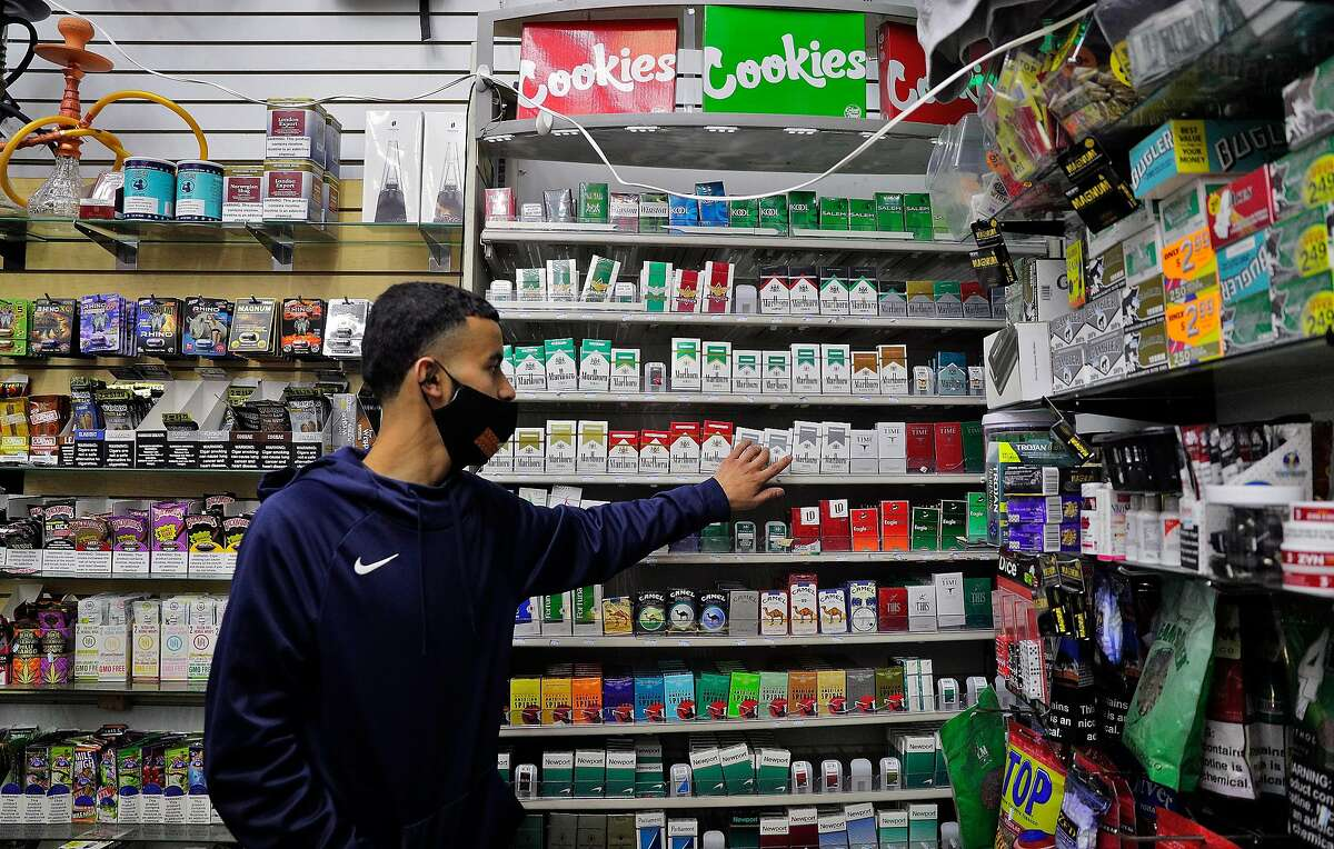 Saqr Abdulla, an employee at Evergreen Smoke Shop in Oakland, points to some of the items that would be banned by a law on flavored cigarettes last month. The ban will be on hold until California voters decide next year whether to uphold it.