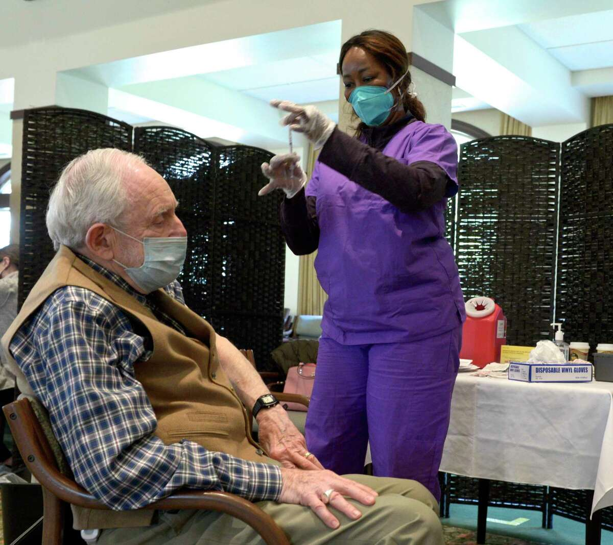Arthur Turner MD, a resident of Meadow Ridge senior living, receives his covid-19 vaccination from Kerrine McCallum RN. Friday, January 22, 2021, in Redding, Conn.