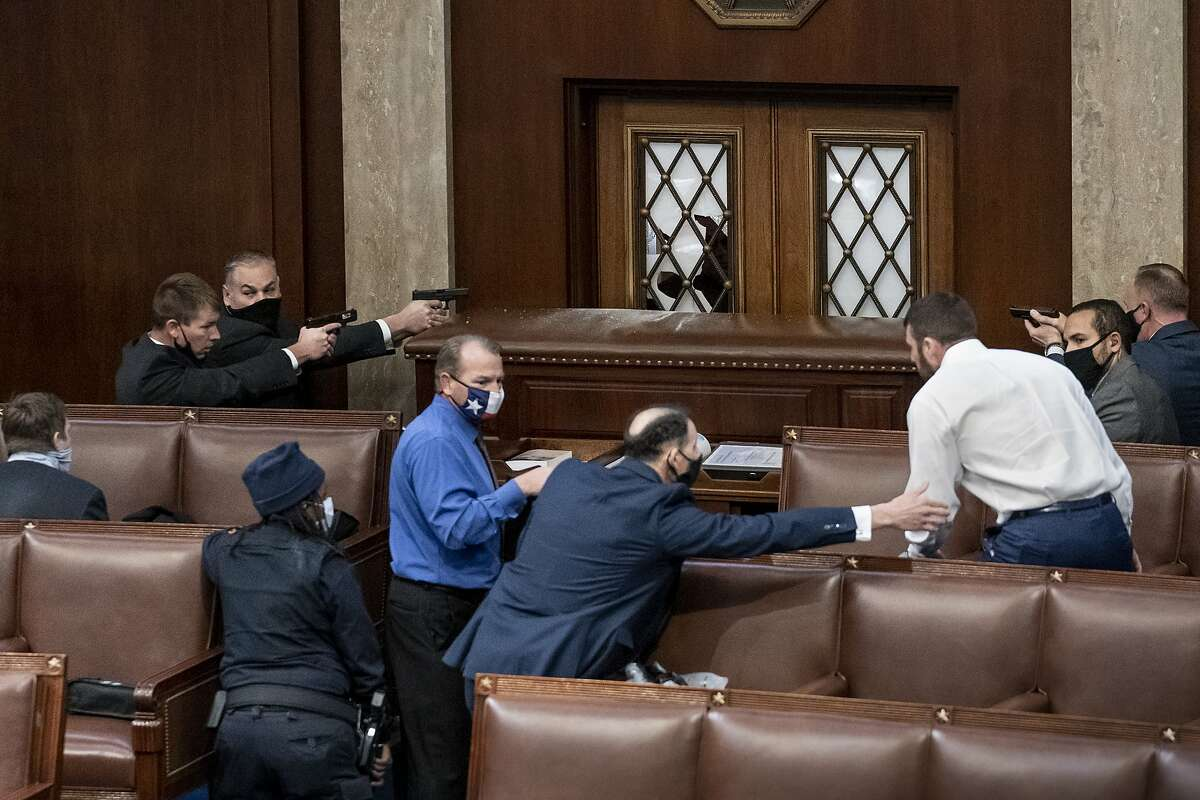 FILE - In this file photo from Jan. 6, 2021, security forces draw their guns as rioters loyal to President Donald Trump try to break into the House of Representatives chamber to disrupt the Electoral College process, at the Capitol in Washington. House Speaker Nancy Pelosi announced today, Friday, Jan. 22, that she will send the article of impeachment against Trump to the Senate on Monday, triggering the start of the former president's trial on a charge of incitement of insurrection over the deadly Capitol riot. (AP Photo/J. Scott Applewhite, File)