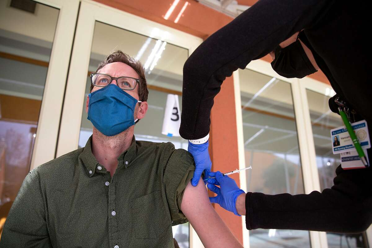 Tyler Paterson, a ninth- and 10th-grade English and English language development teacher at St. Helena High School, receives his first Moderna COVID-19 vaccination at the St. Helena Foundation clinic at Napa Valley College in St. Helena on Thursday.