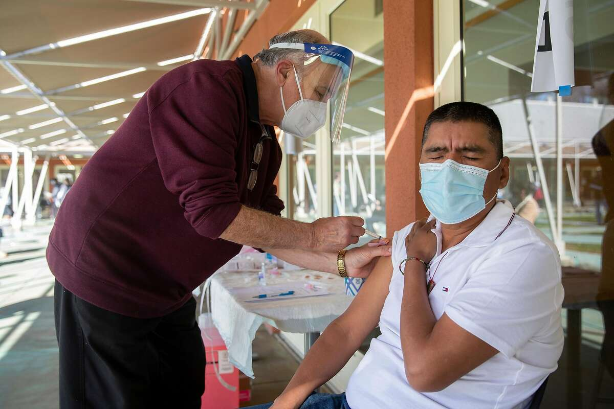 Dr. Joseph Aita administers a COVID-19 vaccination to Carlos Tiburcio, a worker with Renteria Vineyards.