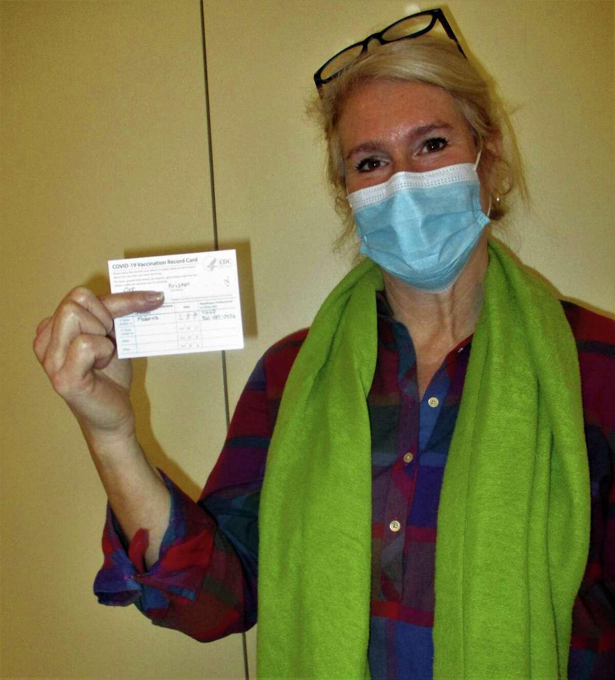 Kristen Orr holding her vaccine card.