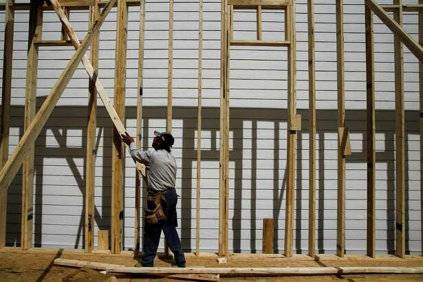 An immigrant construction worker, who declined to give his name but moved here from Mexico, helps build a house in February 2017, off West 23rd Street.