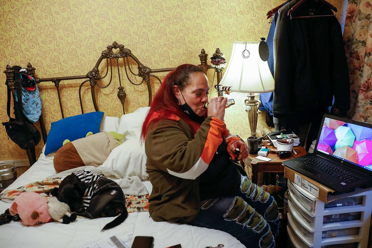 Chucky Torres, who was homeless and trying to get permanent housing, has a drink in her hotel room in San Francisco's Tenderloin last month.