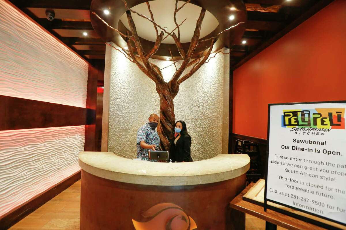 Steve Harmon, assistant general manager talks to hostess Paige Green at Peli Peli South African Kitchen - Galleria Friday, Jan. 22, 2021, in Houston. Peli Peli survived the pandemic, but with fewer workers and an adjusted business model