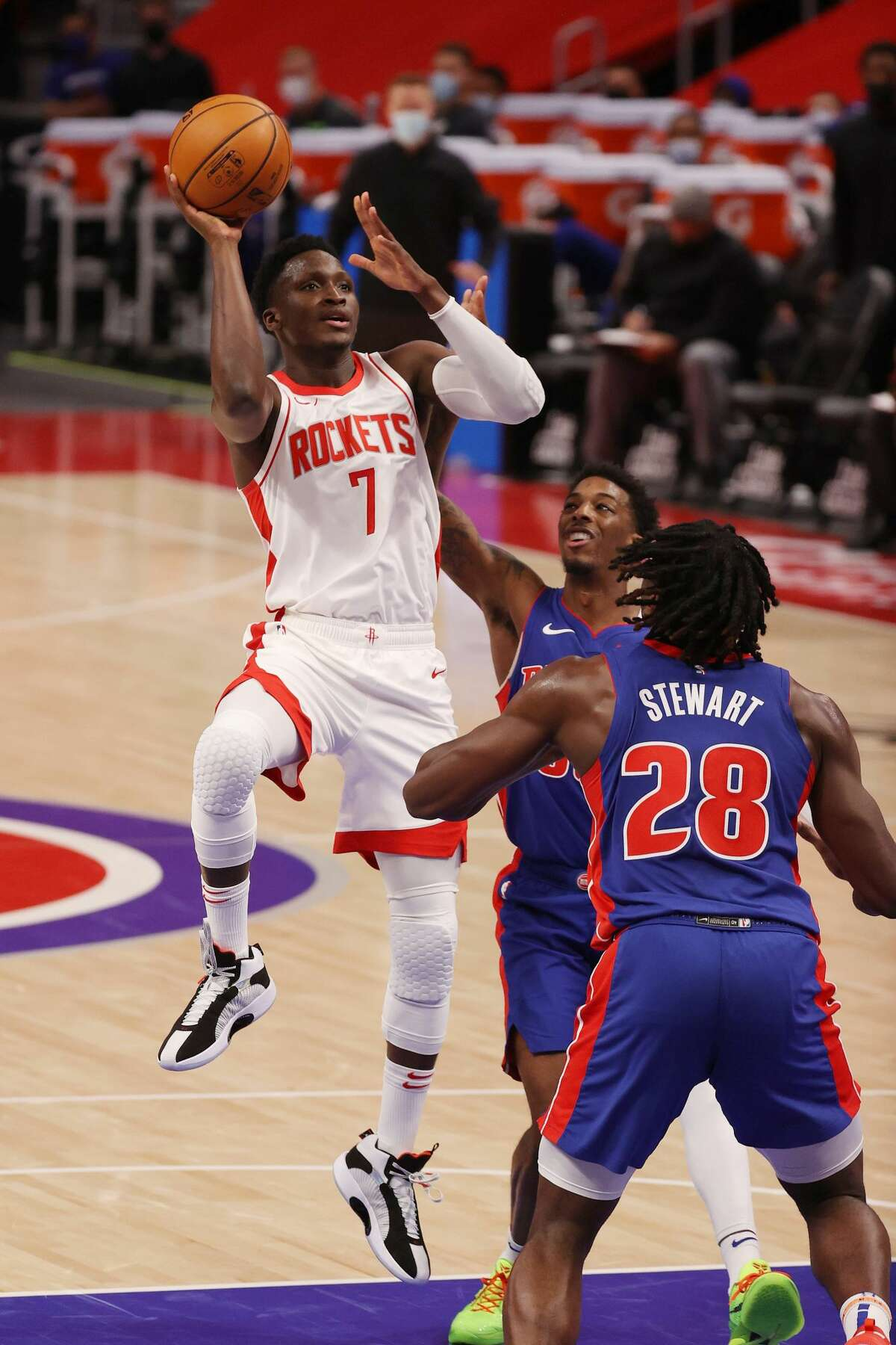 DETROIT, MICHIGAN - JANUARY 22: Victor Oladipo #7 of the Houston Rockets drives to the basket against Delon Wright #55 and Isaiah Stewart #28 of the Detroit Pistons during the first half at Little Caesars Arena on January 22, 2021 in Detroit, Michigan. NOTE TO USER: User expressly acknowledges and agrees that, by downloading and or using this photograph, User is consenting to the terms and conditions of the Getty Images License Agreement. (Photo by Gregory Shamus/Getty Images)