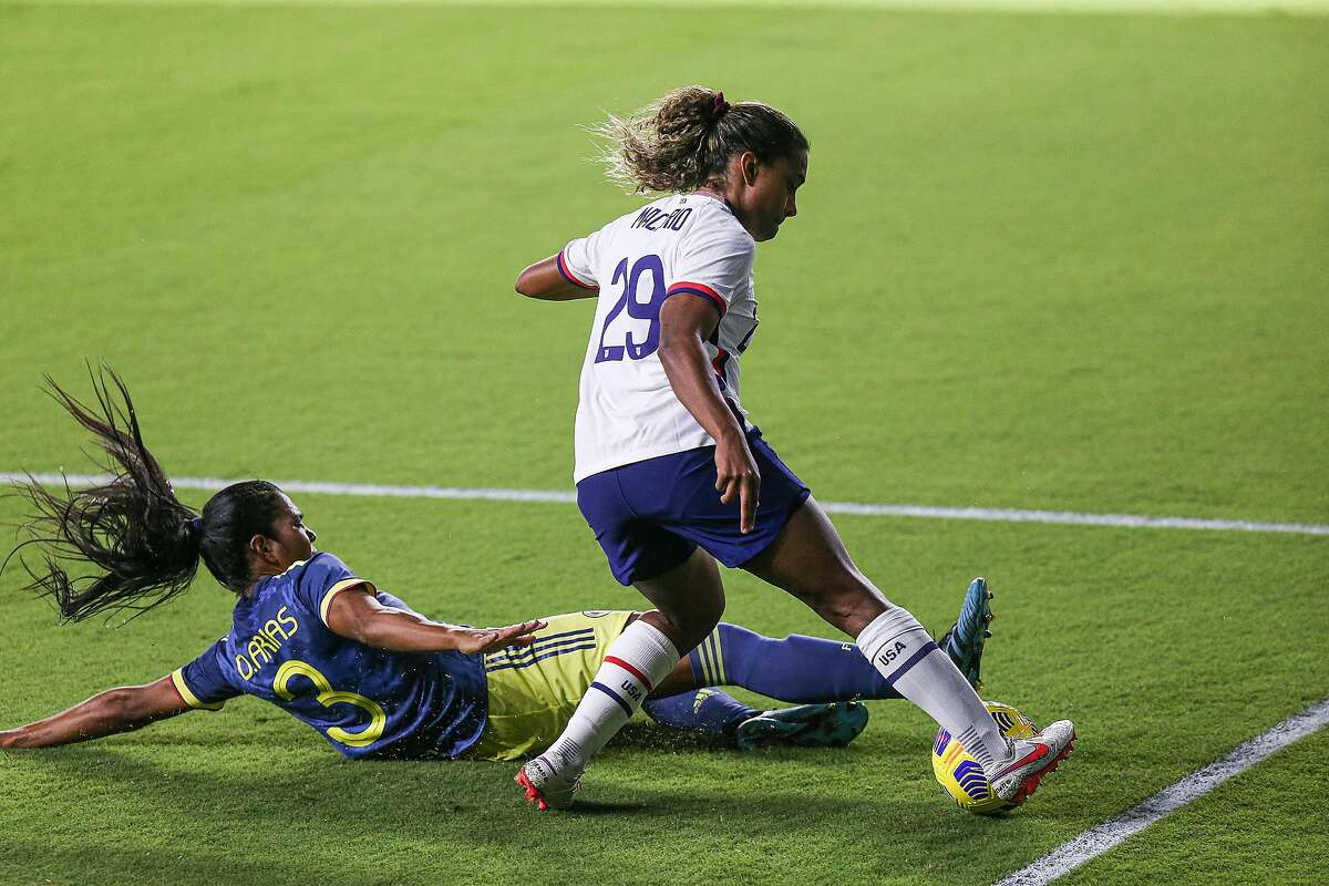 ORLANDO, FL - JANUARY 22: Catarina Macario #29 of United States avoids the tackle from Daniela Arias #3 of Columbia at Exploria Stadium on January 22, 2021 in Orlando, Florida. (Photo by Alex Menendez/Getty Images)