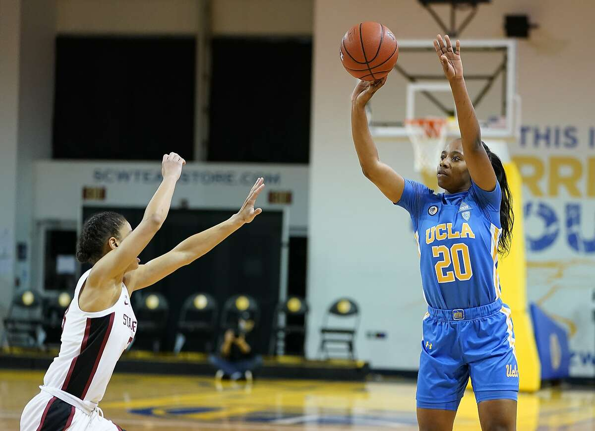 UCLA guard Charisma Osborne (20) takes a three-point shot against Stanford guard Anna Wilson (3) during the first half of an NCAA college basketball game in Santa Cruz, Calif., Friday, Jan. 22, 2021. (AP Photo/Tony Avelar)